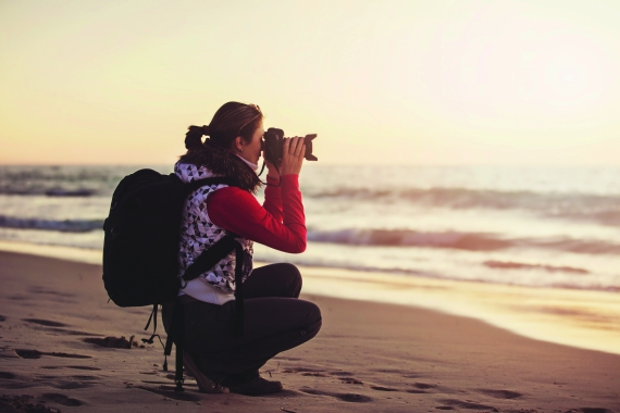 Young woman photographer with backpack taking pictures with SLR camera at sunset on the winter beach.